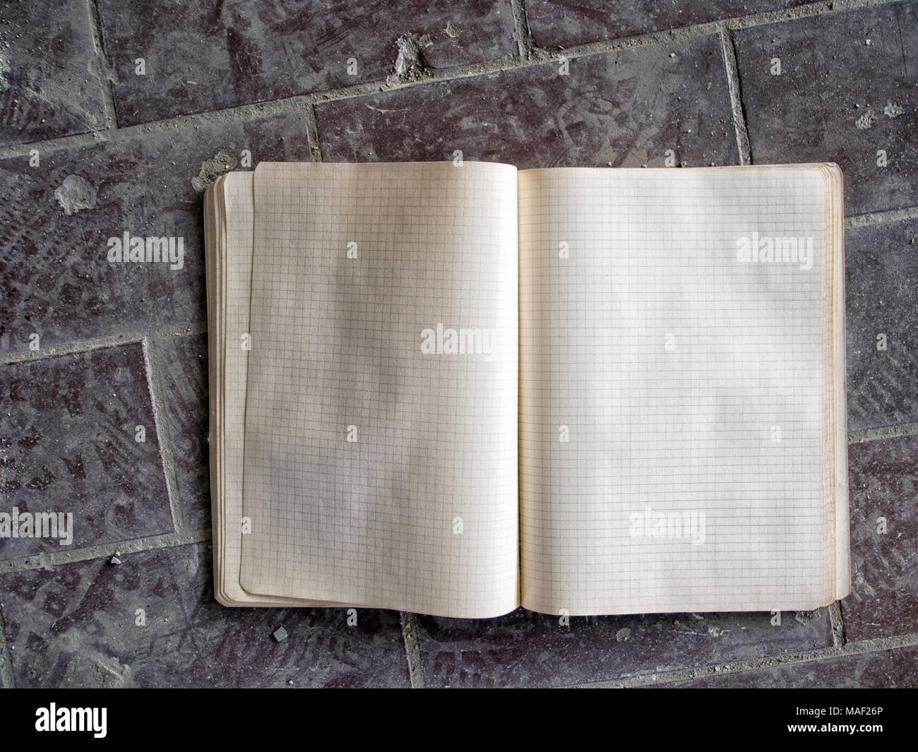 Old school copy book, abandoned in dust. Squared paper. - Stock Image