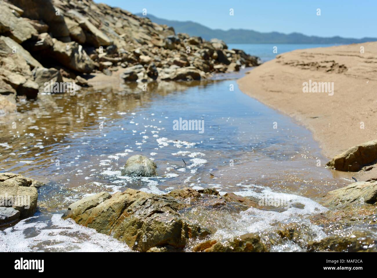 Water flowing out of a small creek at low tide, Shelly Cove trail at Cape Pallarenda Conservation Park Queensland Australia - Stock Image