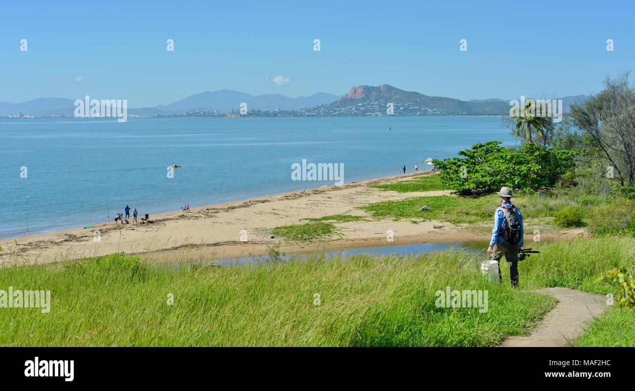 Fisherman walking down a path with a view of castle hill from pallarenda, Shelly Cove trail at Cape Pallarenda Conservation Park Queensland Australia - Stock Image