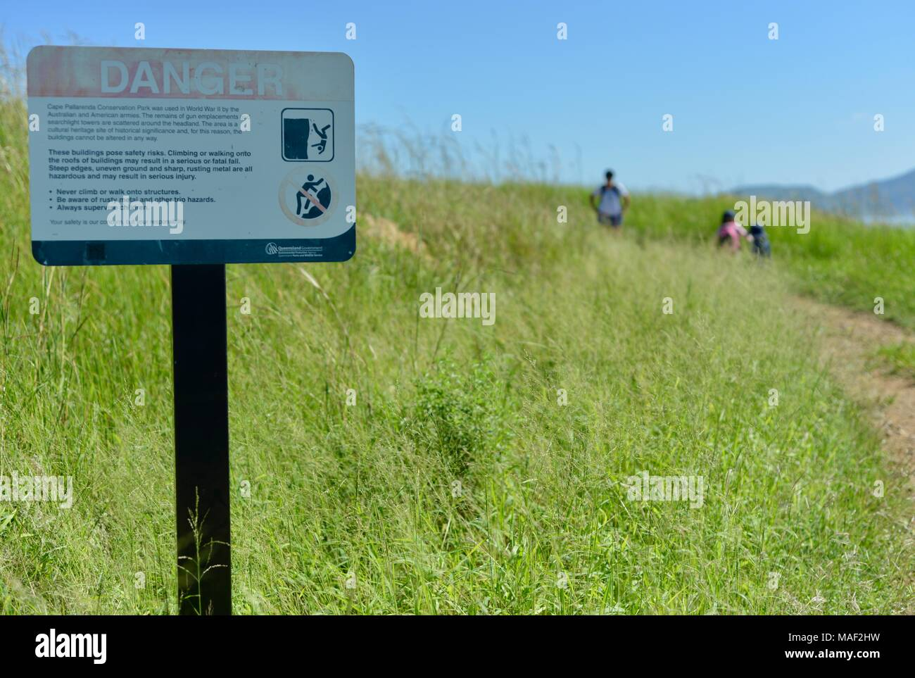 Mother and two daughters walk past a danger cliff face sign on Shelly Cove trail at Cape Pallarenda Conservation Park Queensland Australia - Stock Image