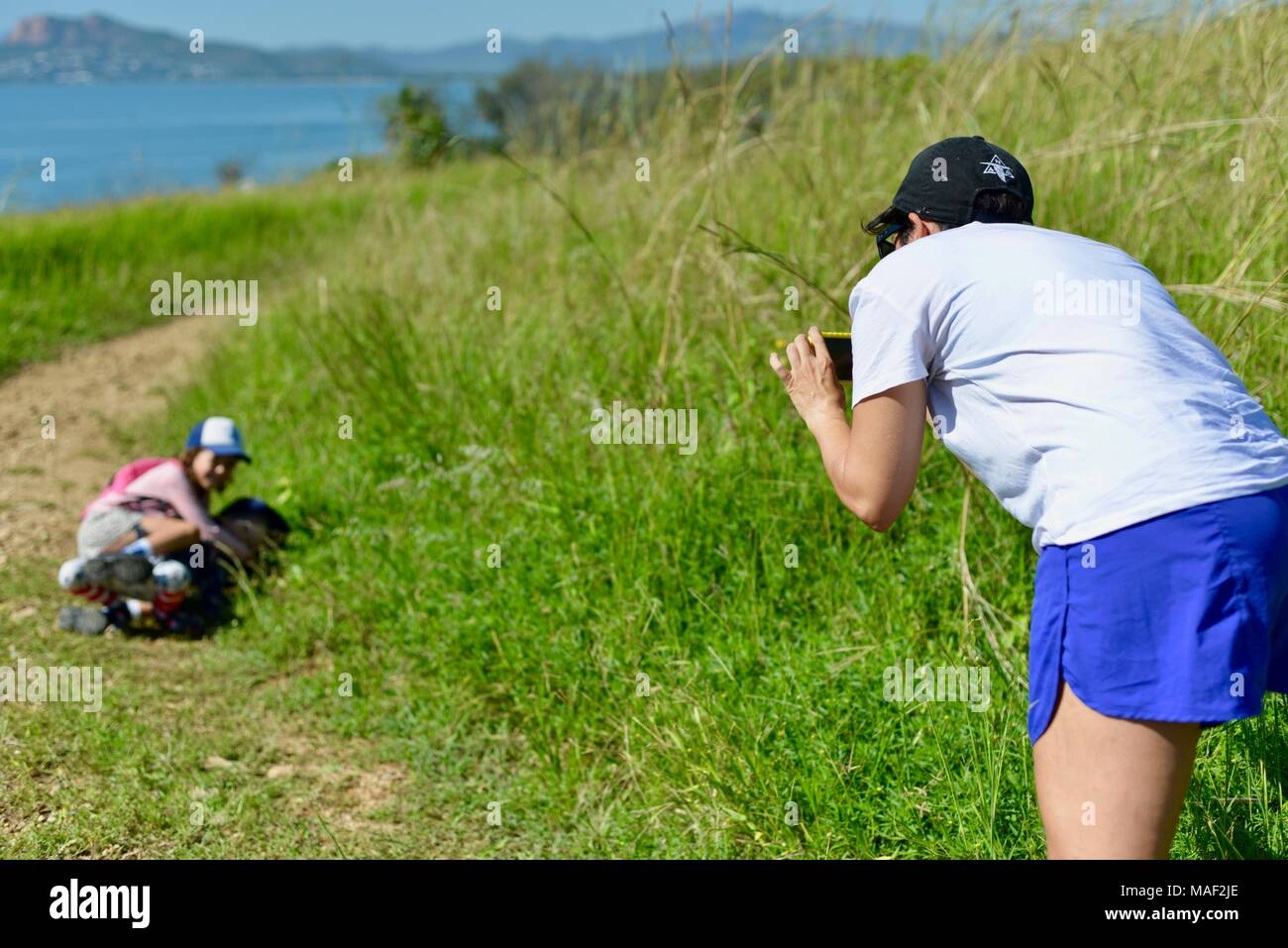 Mother taking picture of children with mobile phone on family trip, Shelly Cove trail at Cape Pallarenda Conservation Park Queensland Australia - Stock Image