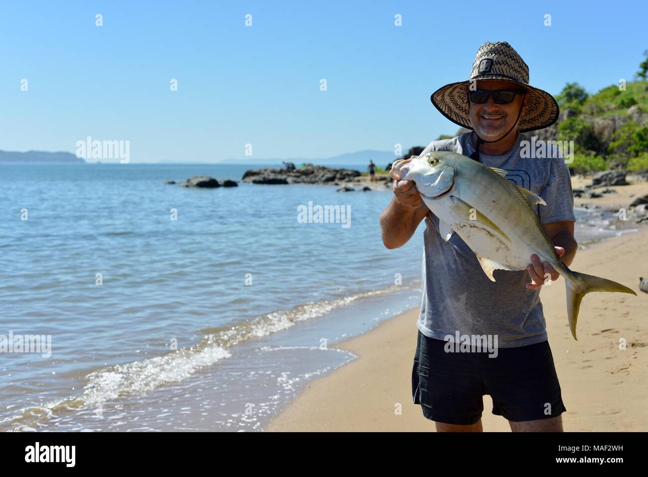 Proud fisherman with fresh catch of the day, probably Giant Trevally (Caranx ignobilis) Shelly Cove trail at Cape Pallarenda Conservation Park - Stock Image