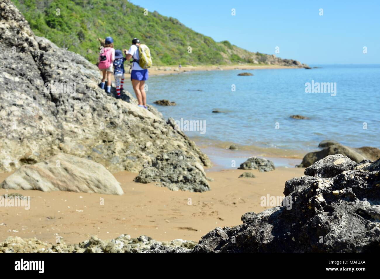 Mother and two daughters walk near the ocean tropical beach and forest, Shelly Cove trail at Cape Pallarenda Conservation Park Queensland Australia - Stock Image