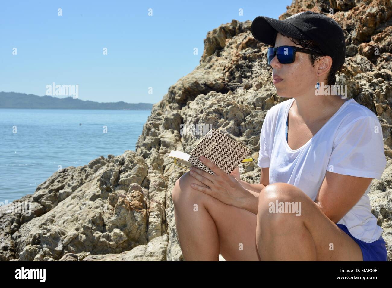 Woman writing near the beach for inspiration, Shelly Cove trail at Cape Pallarenda Conservation Park Queensland Australia - Stock Image