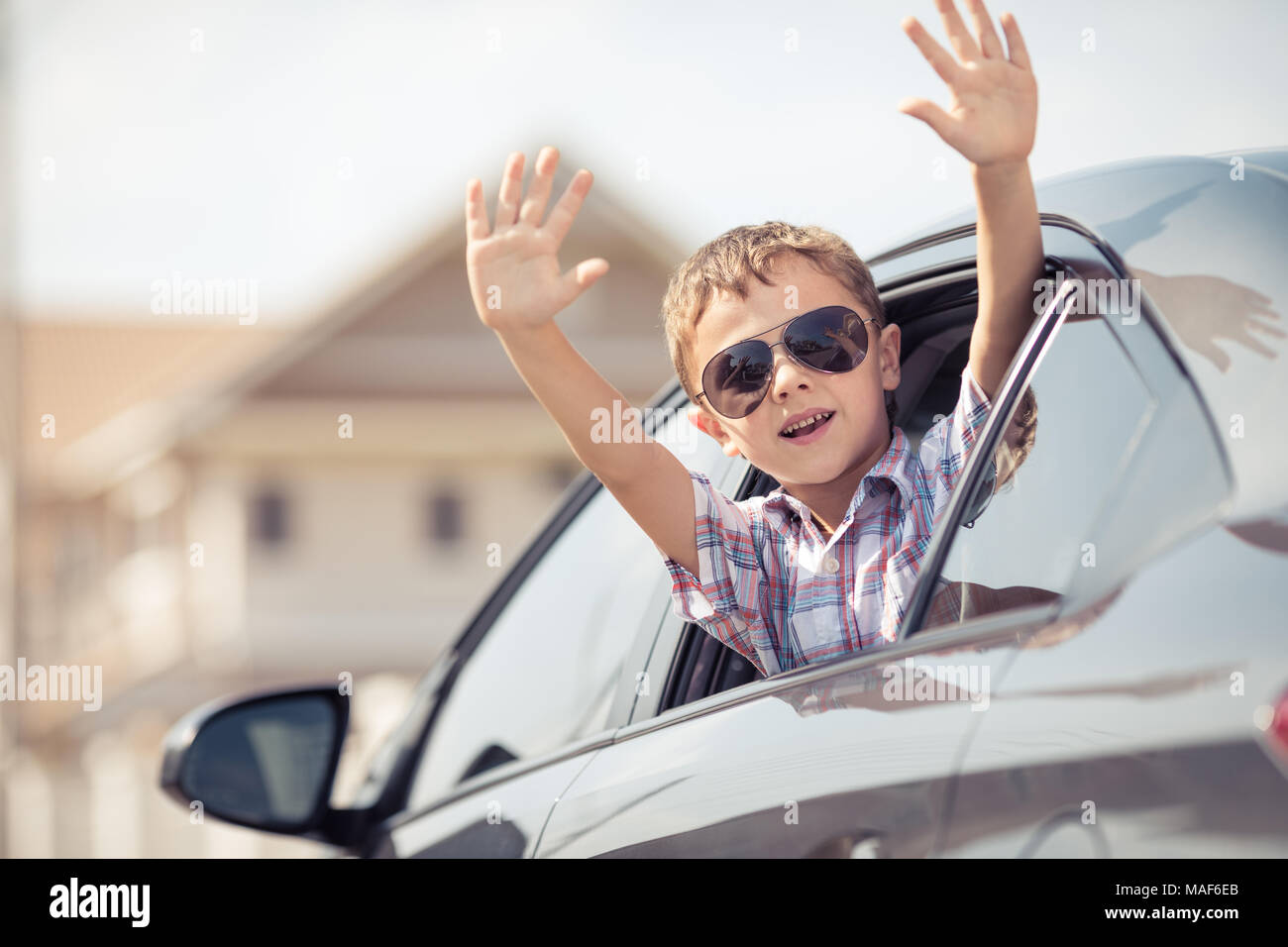 One happy little boy sitting in the car at the day time. Concept of summer vacation. - Stock Image