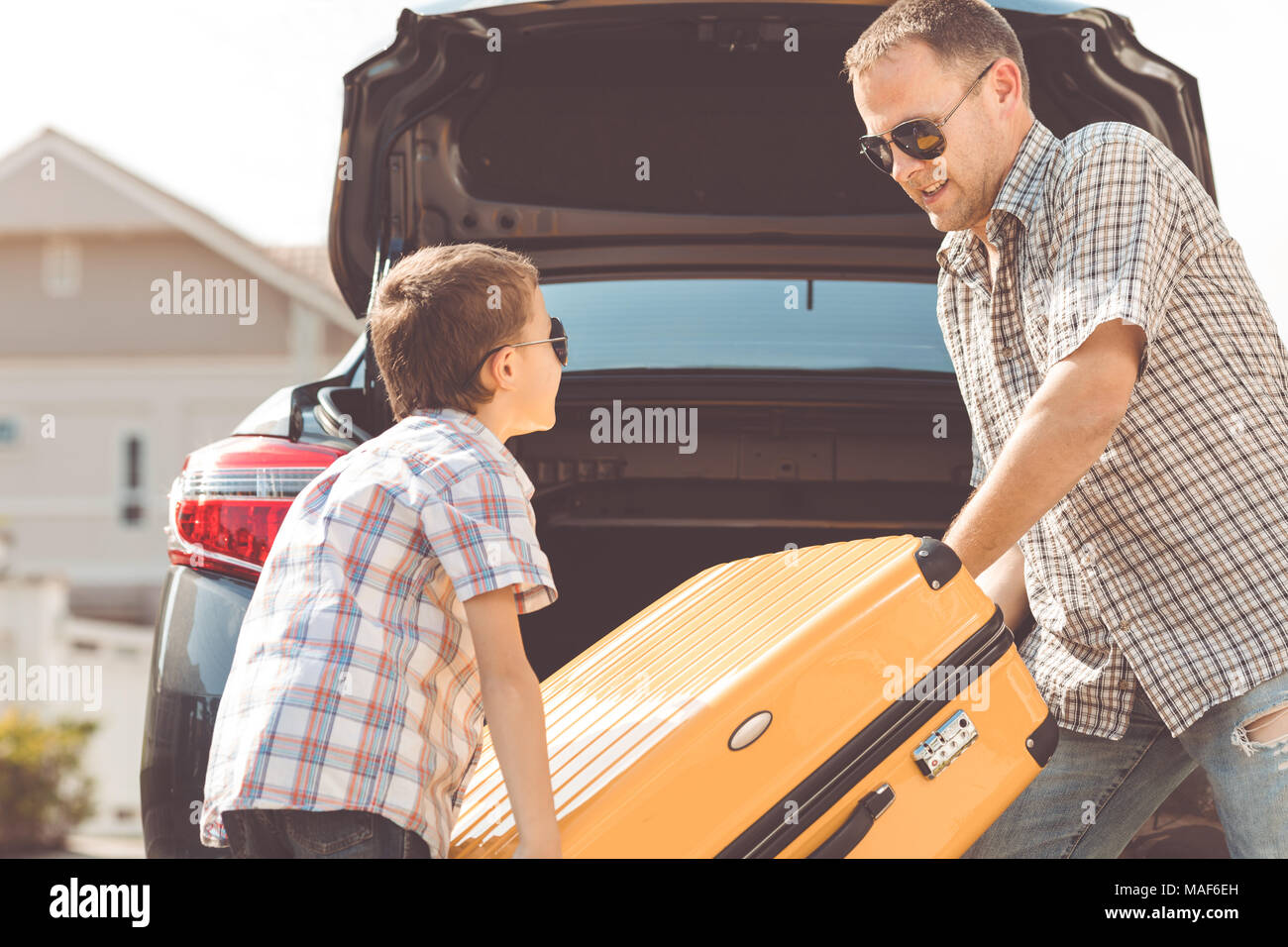 Happy father and son getting ready for road trip on a sunny day. Concept of friendly family. - Stock Image