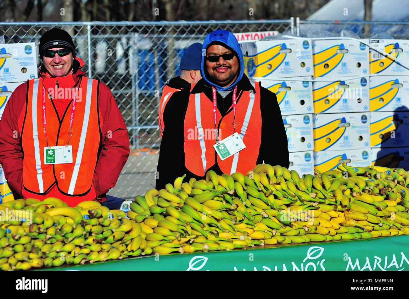 Chicago, Illinois, USA. Volunteers dressed for cold temperature staff a banana supply for runners that finish the Shamrock Shuffle 8K race. - Stock Image