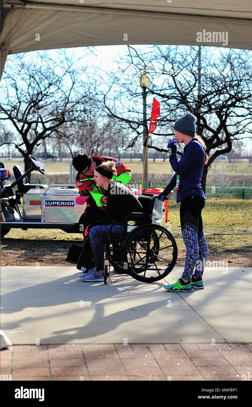Chicago, Illinois, USA. After collapsing at the finish line, a runner received fast attention at the medical tent at the 2018 Shamrock Shuffle race. - Stock Image