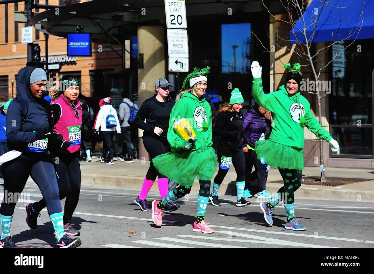 Chicago, Illinois, USA. Runners, mostly reduced to walking, near the end of the field and nearing the end of the 2018 Shamrock Shuffle race in Chicago. - Stock Image