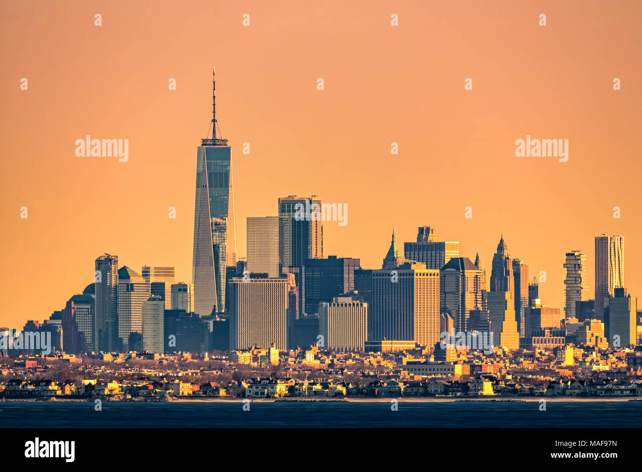 New York highrise skyline with lowrise Brooklyn borough in the foreground, as viewed at sunrise, from Sandy Hook, NJ. - Stock Image