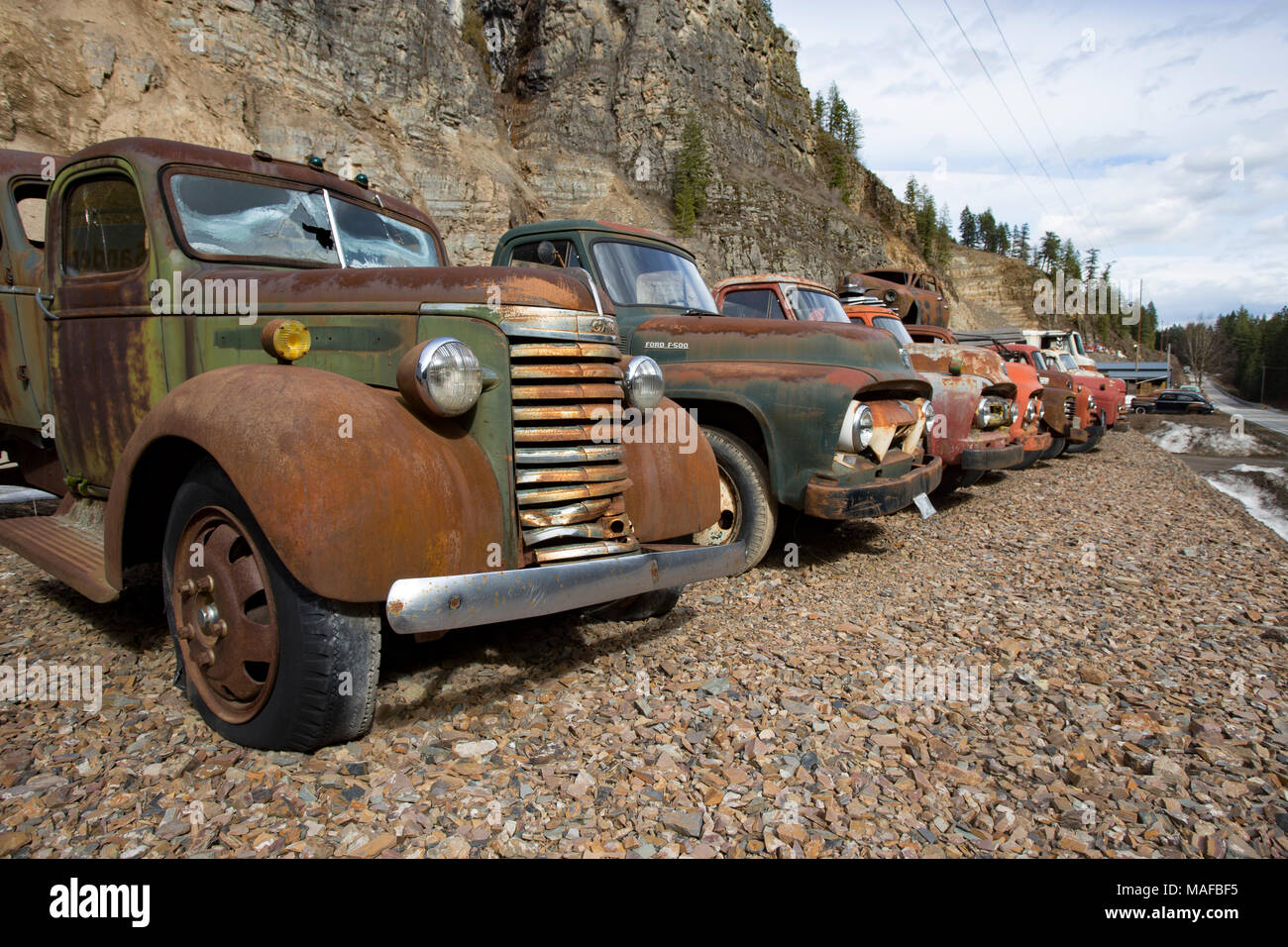 A 1939 GMC work truck, in a line of old trucks, at an old stone ...