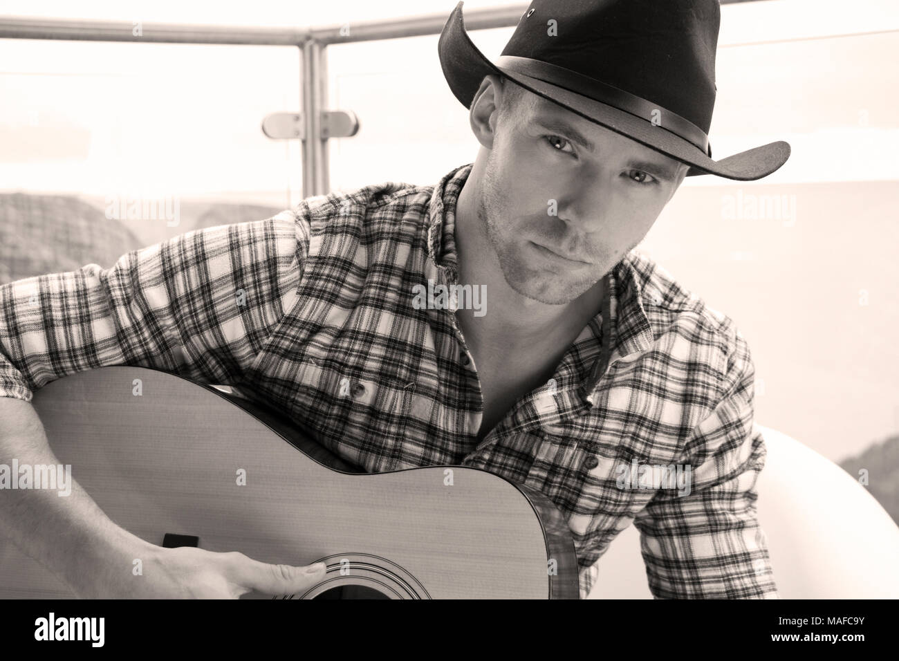 935e3c612ac41 Handsome country and western cowboy singer wearing hat and playing guitar  on hotel balcony with ocean
