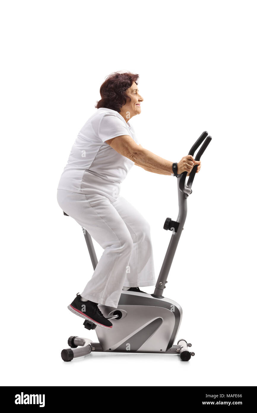 Elderly woman working out on a stationary bike isolated on white background - Stock Image