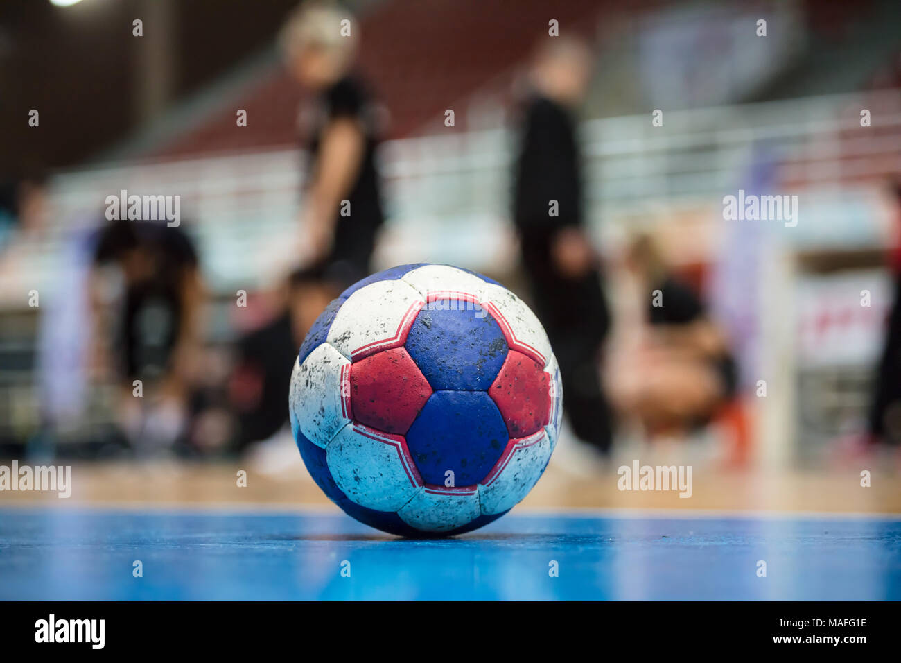 Handball ball on court' s floor. Ready for the match. Blurred referees, coaches and athletes and field background. - Stock Image