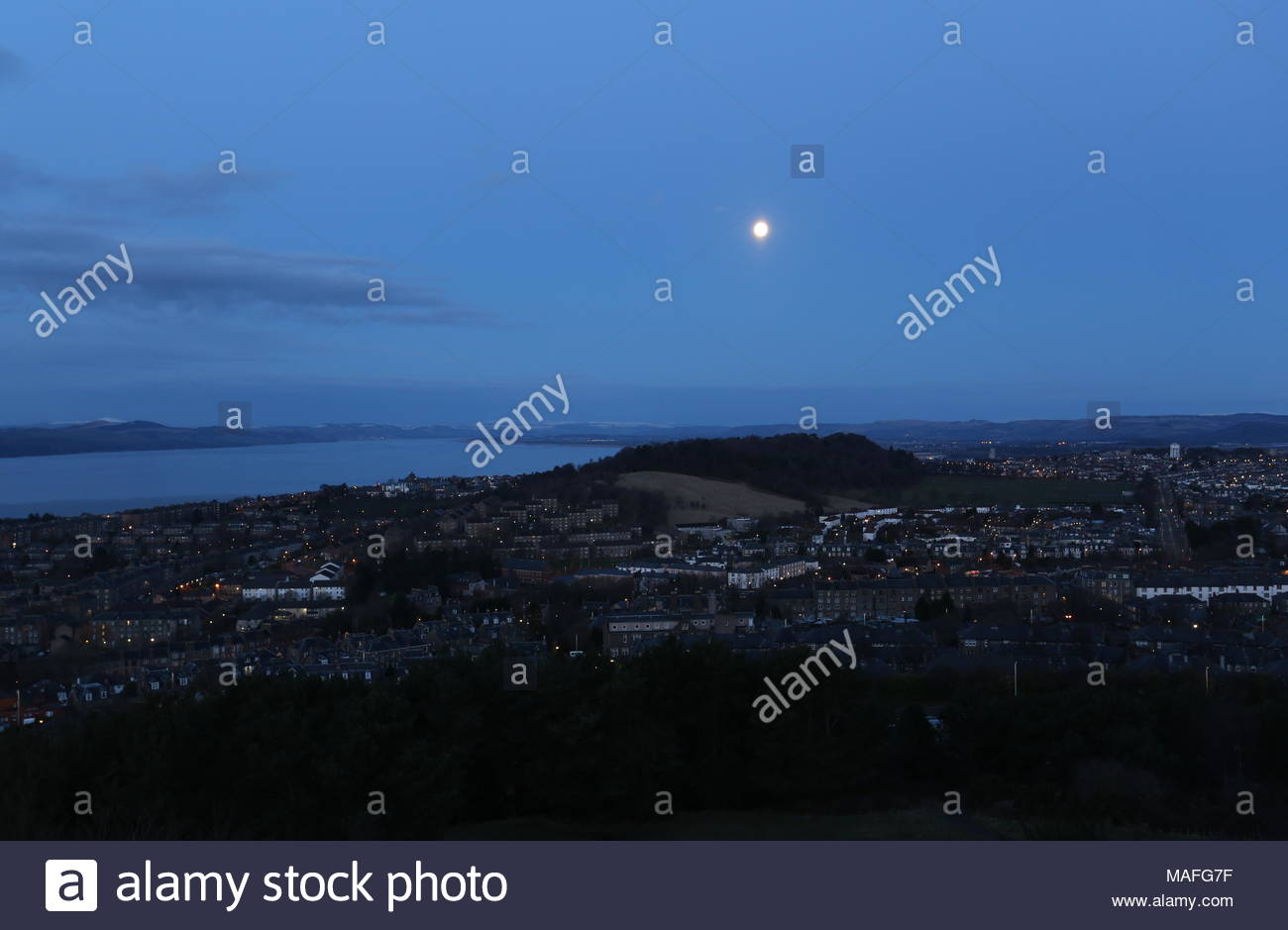 Full moon over Lochee Park Dundee Scotland  April 2018 - Stock Image