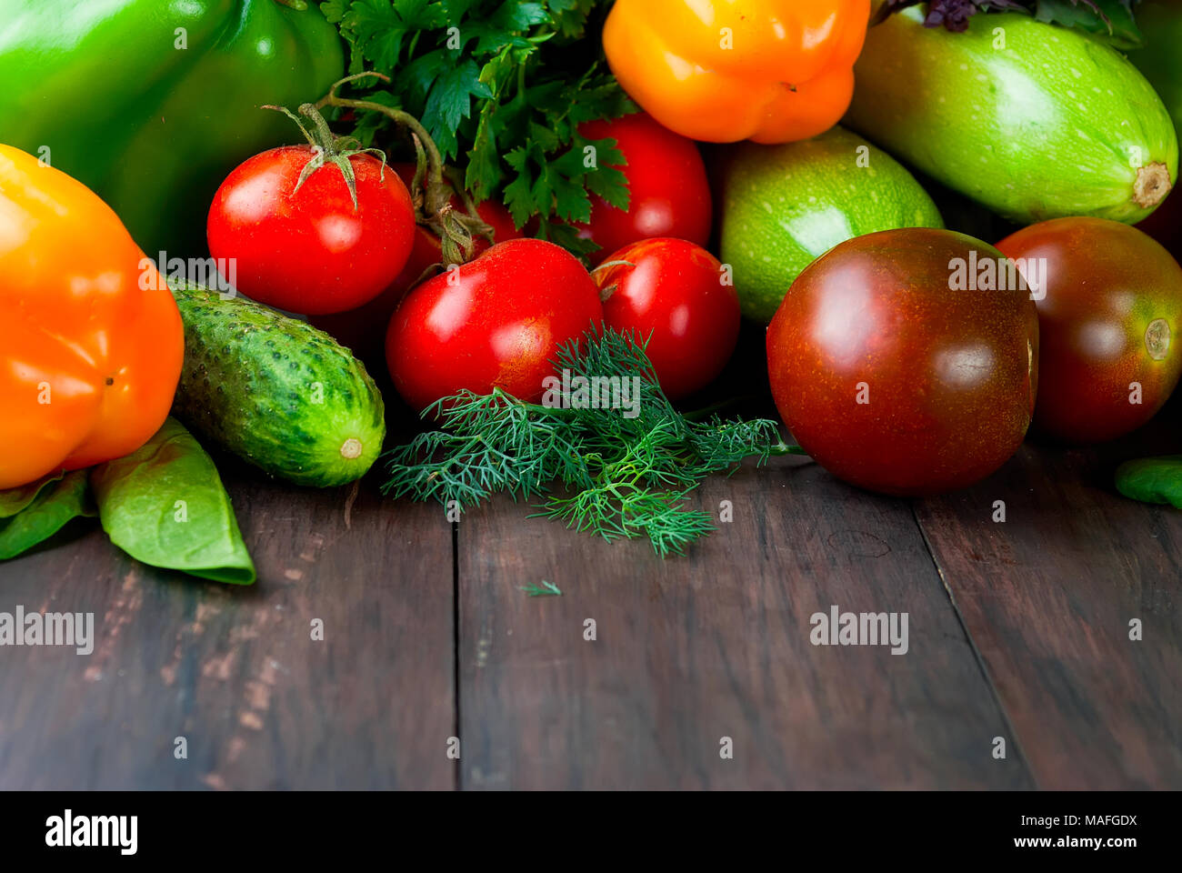 green and red color vegetables,  tomatoes, cucumber, peppers, fragrant herbs on an old wooden table, Top view, copy space Stock Photo