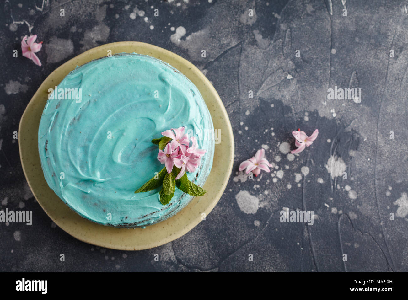 Blue stylish cake with flowers and mint. Copy space, dark background - Stock Image