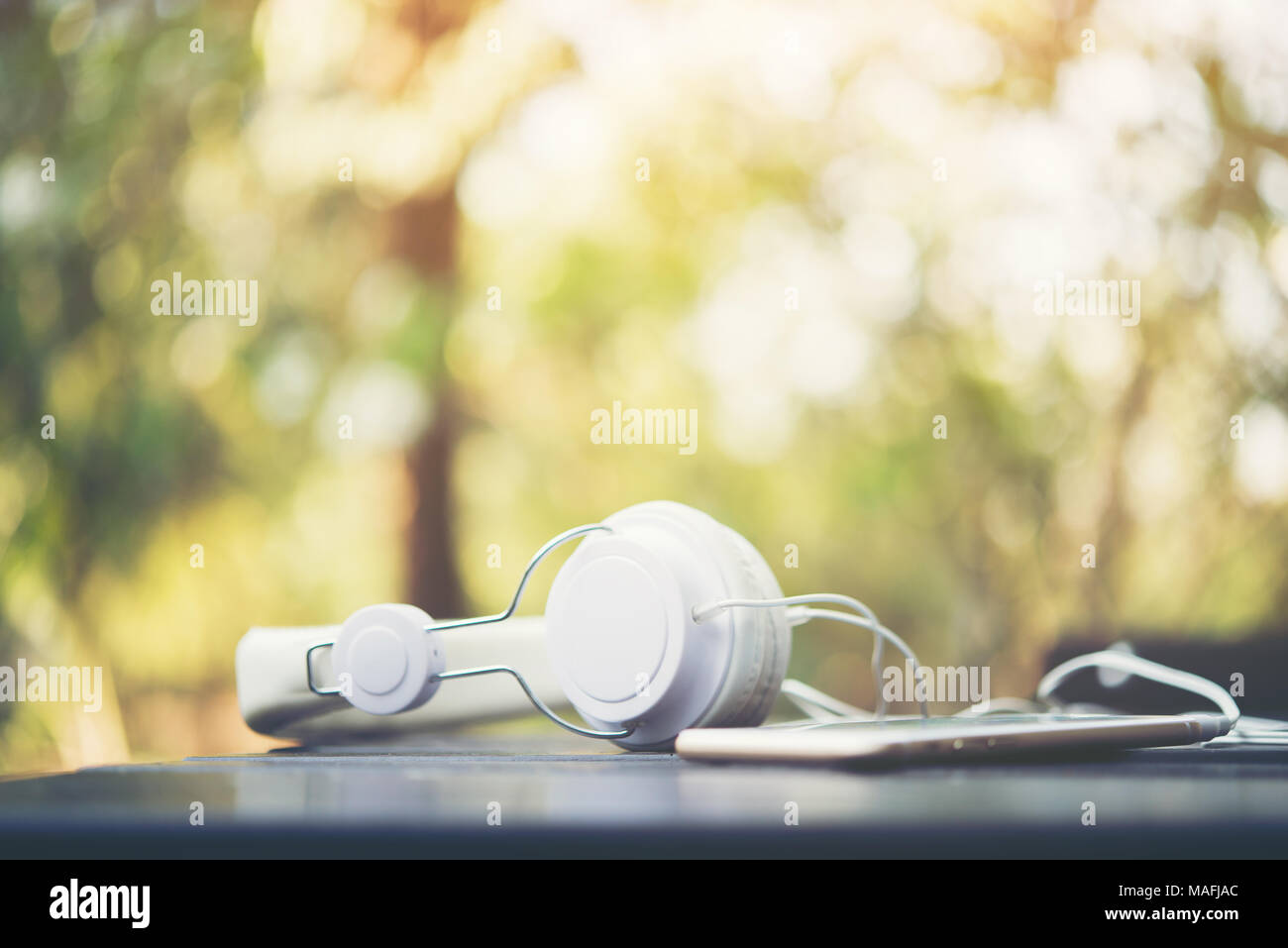 Mobile Phone With Headphone On Wooden Table With Nature Background Vintage Filter Stock Photo Alamy