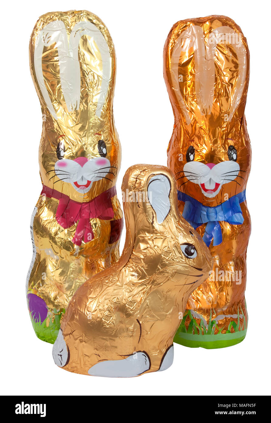 Foil-wrapped chocolate Easter bunny family. Isolated. - Stock Image