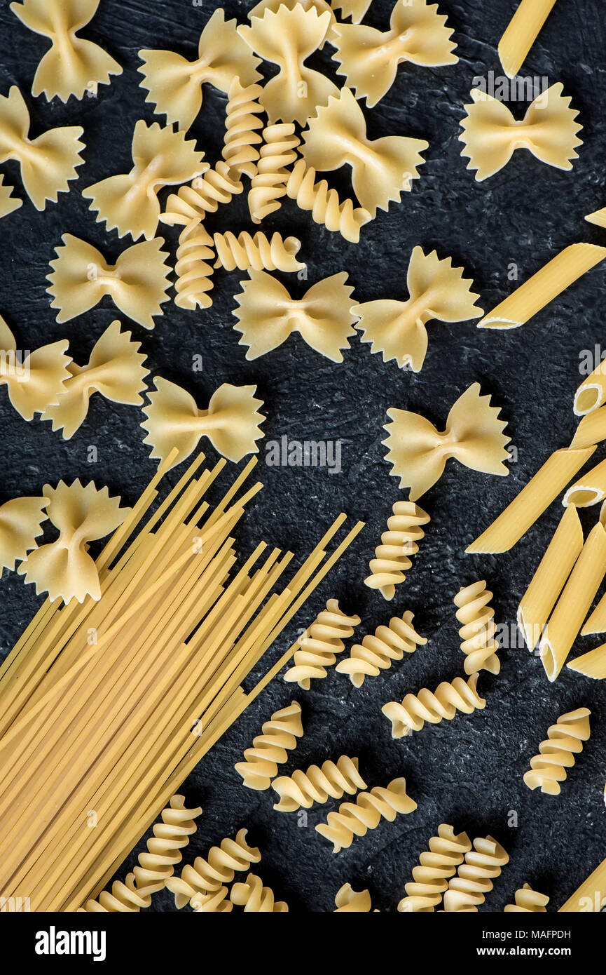 Assorted uncooked raw pasta on black background. Italian pasta: penne, farfalle, spaghetti, fusilli. - Stock Image