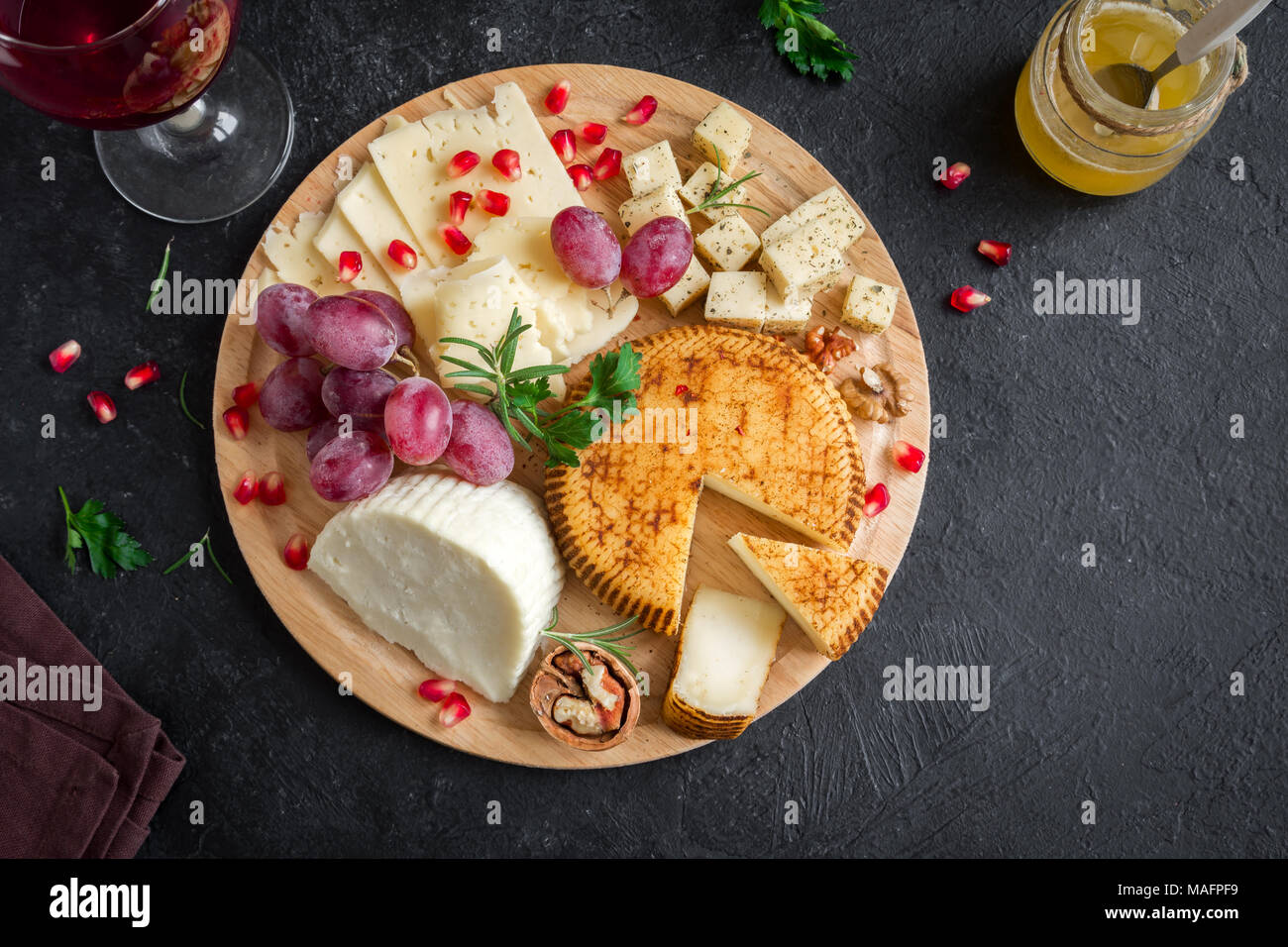 Cheese platter with assorted cheeses, grapes, nuts over black background, copy space. Italian cheese and fruit platter with honey and wine. - Stock Image