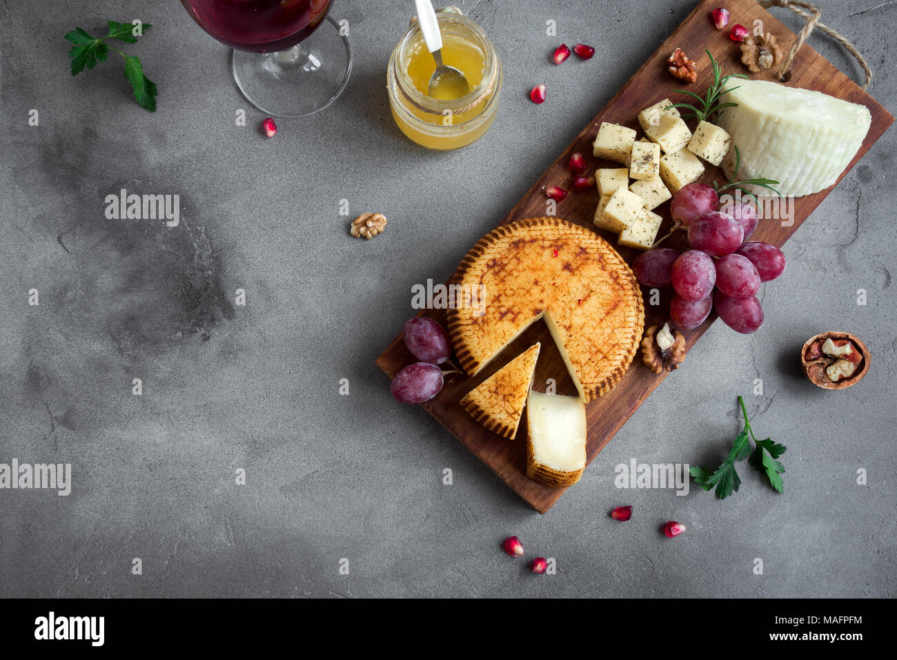 Cheese platter with assorted cheeses, grapes, nuts over concrete background, copy space. Italian cheese and fruit platter with honey and wine. - Stock Image