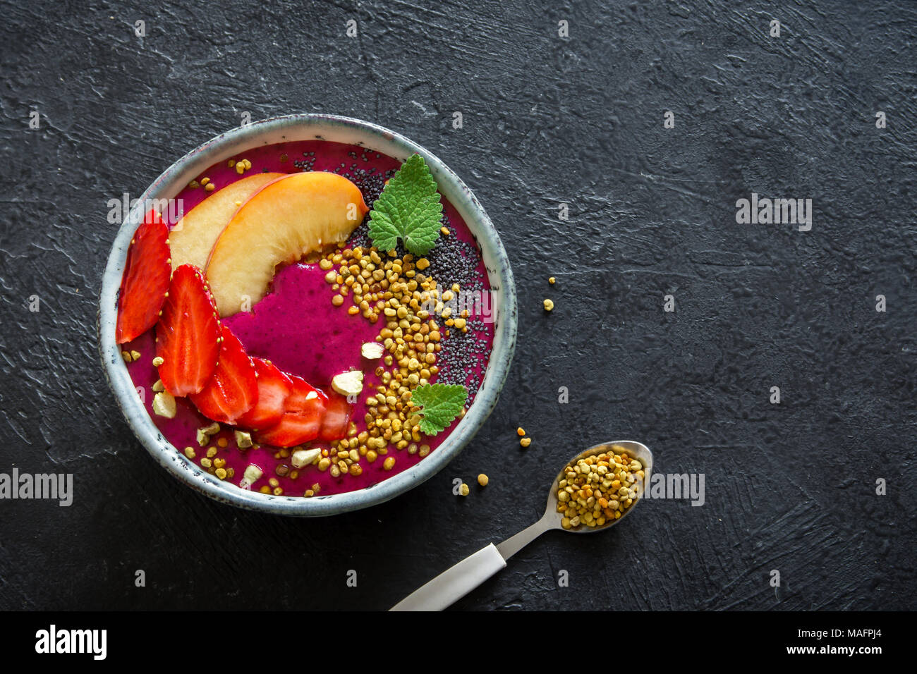Acai smoothie bowl with chia seeds, fruits, berries (strawberries) and bee pollen for healthy vegan vegetarian diet raw breakfast. Breakfast smoothie  - Stock Image