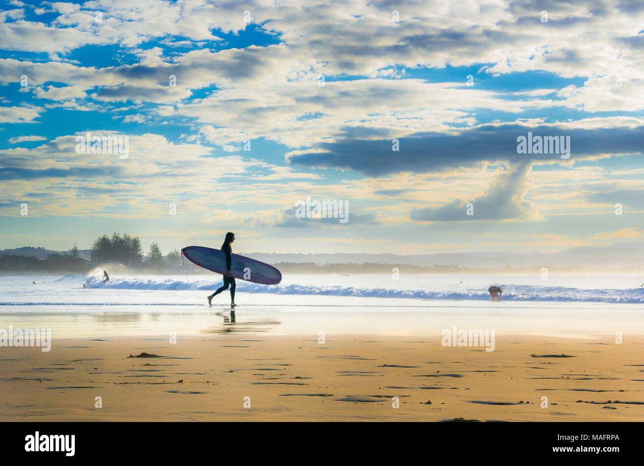 Surfer entering the surf at The Pass, Byron Bay, New South Wales, Australia - Stock Image