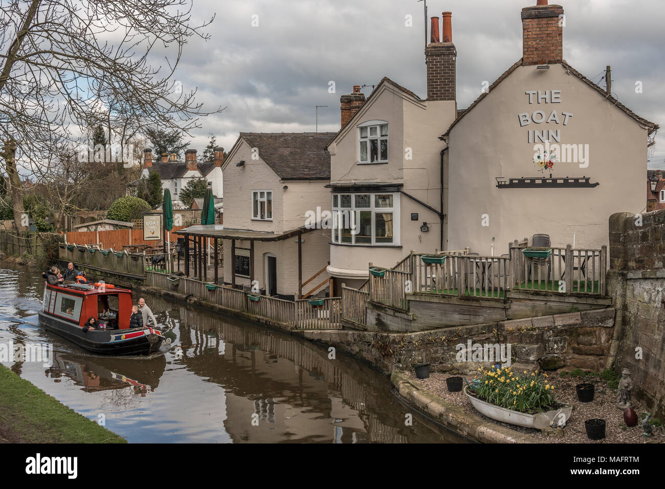 Gnosall, Staffordshire, UK - April 1st 2018 - A canal boat with people enjoy a trip in a narrowboat passing a canal side pub / inn with reflections in - Stock Image