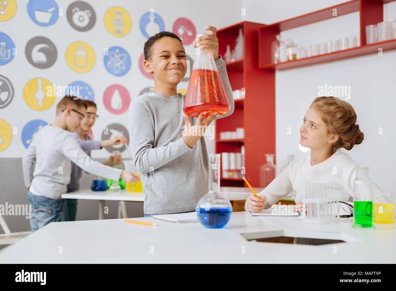 Upbeat boy checking out flask with red chemical - Stock Image