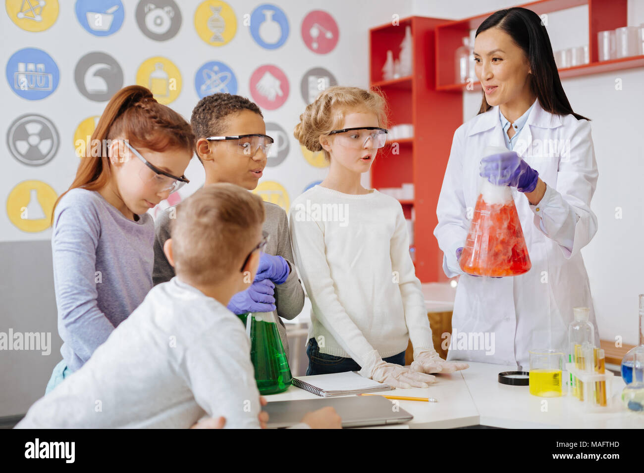 Pleasant teacher commenting about ongoing chemical reaction Stock Photo
