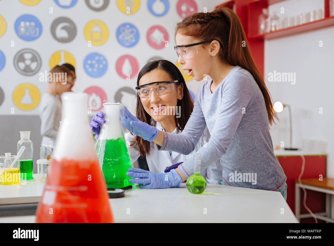Surprised teacher and student being surprised with chemical reaction - Stock Image
