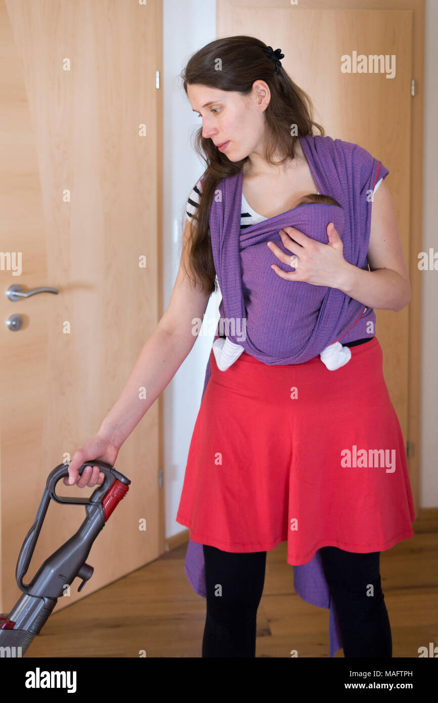 A mother carrying her baby in a sling and hoovering - concept, multi-tasking - Stock Image