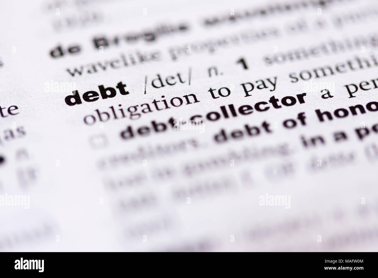 A macro shot showing the definition of the word debt in an English dictionary - Stock Image