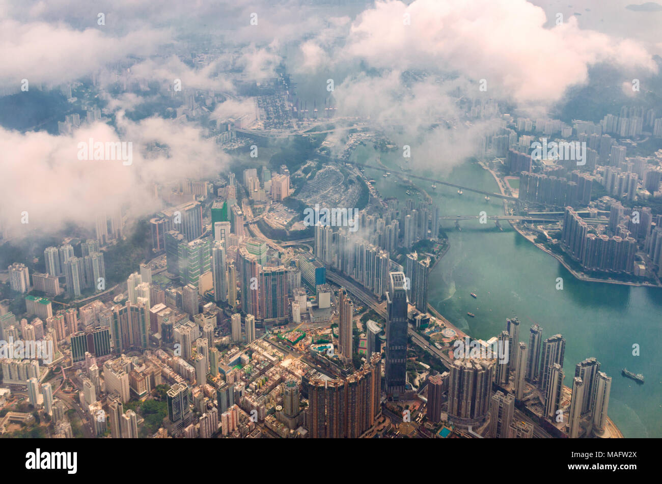 Aerial view through the clouds to a large metropolis city of Hong Kong. - Stock Image