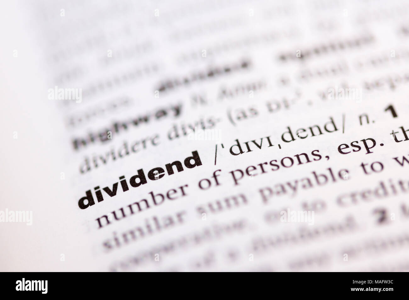 A macro shot showing the definition of the word dividend in an English dictionary - Stock Image