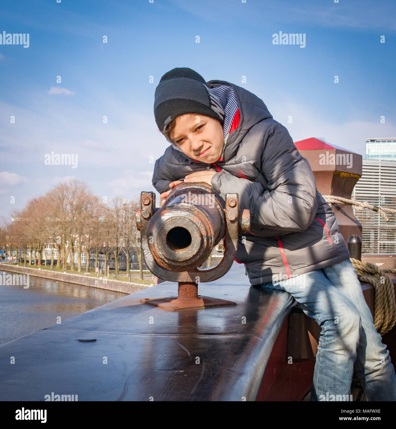 Boy aiming a canon at a target, on an old sailing ship, Amsterdam, Holland. Vintage vessel. - Stock Image