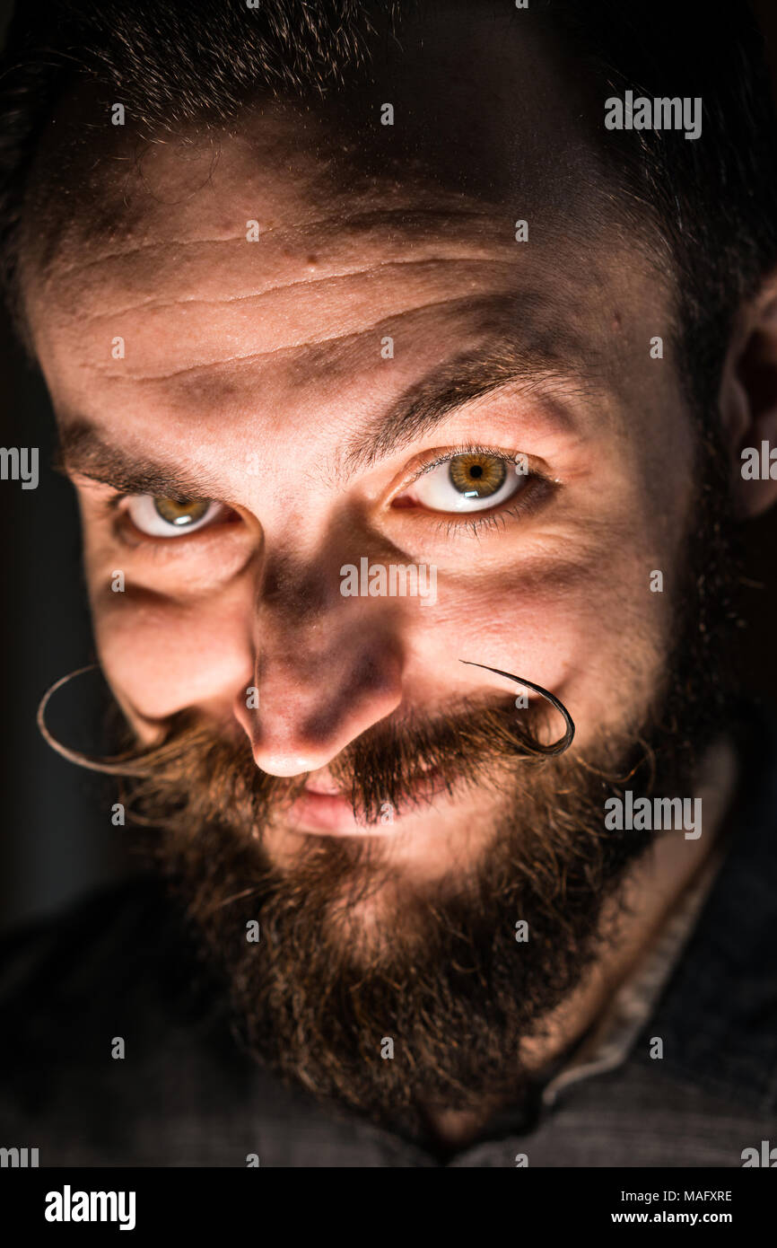 Inventor Hipster with Beard and Mustages in the Dark Room. Smiling Trickster. - Stock Image