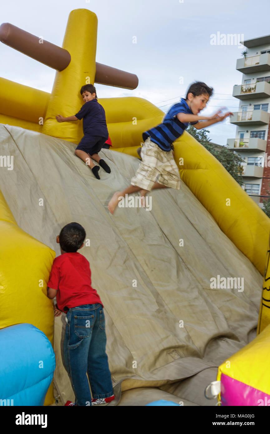 Miami Beach Florida Flamingo Park School's Out Fiesta celebration community event inflatable playground amusement boy child play - Stock Image