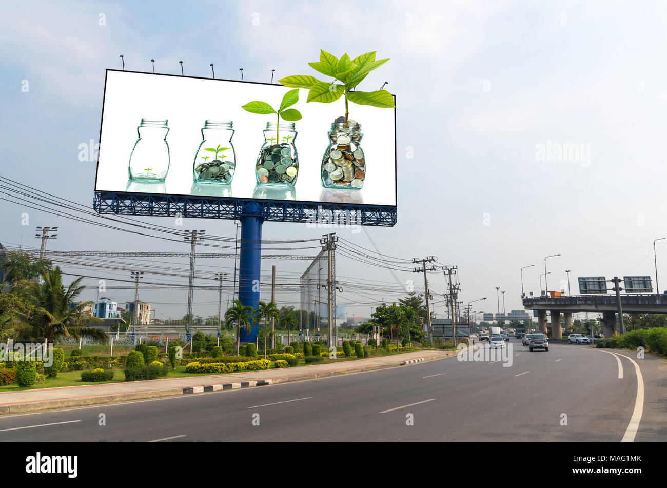 Billboard showing the mix coins and seed in clear bottle on white background for advertisement, Business investment growth concept - Stock Image