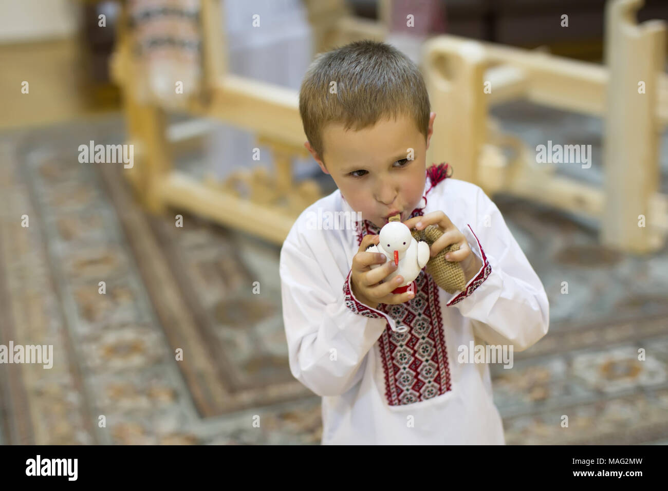 The Belarusian boy. Belarusian boy in national clothes with a toy clay cockerel. Children's ethnic ancient Slavic toys.A boy with a toy whistle - Stock Image