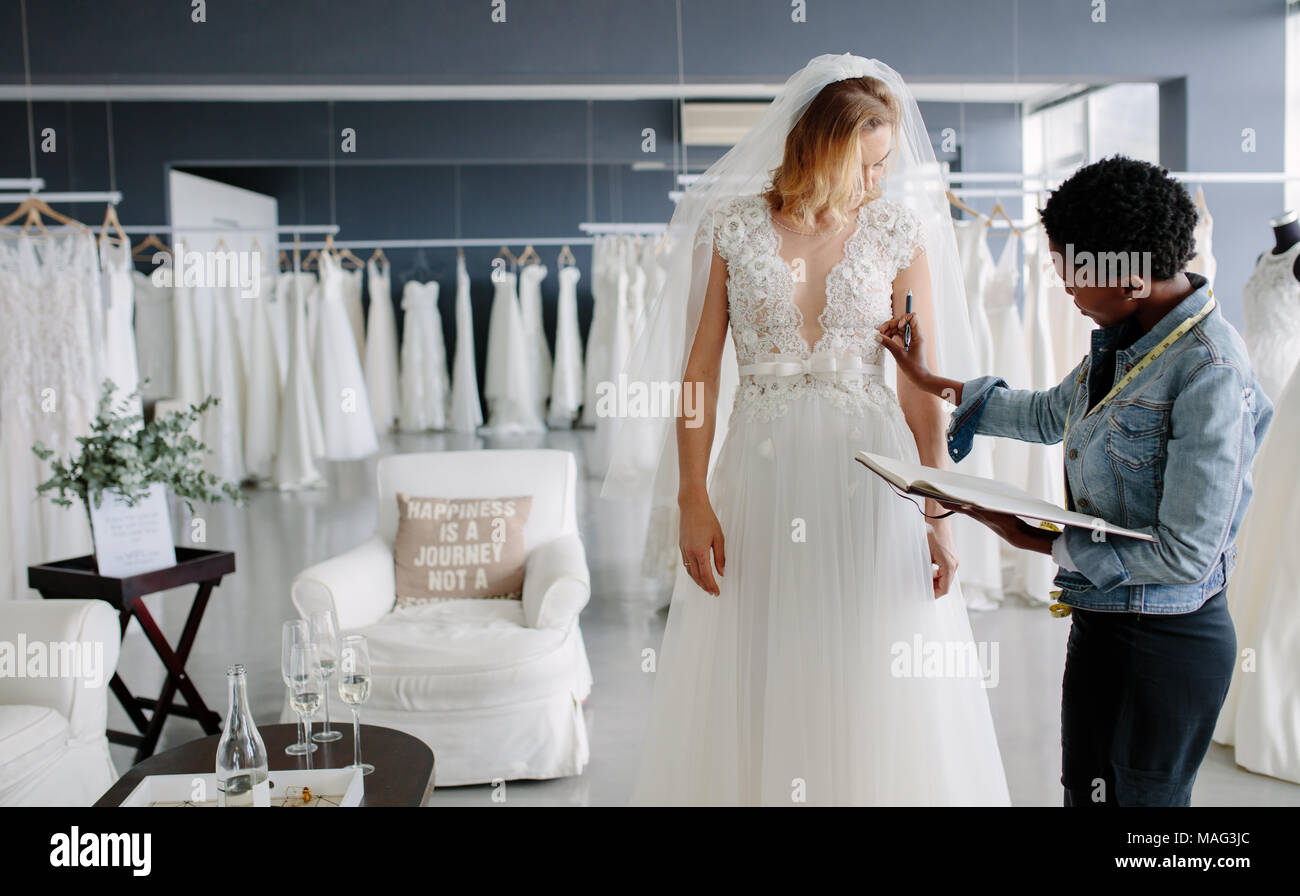 Dress designer fitting bridal gown to woman in boutique. Women checking and making adjustment to wedding gown in professional fashion designer studio. - Stock Image