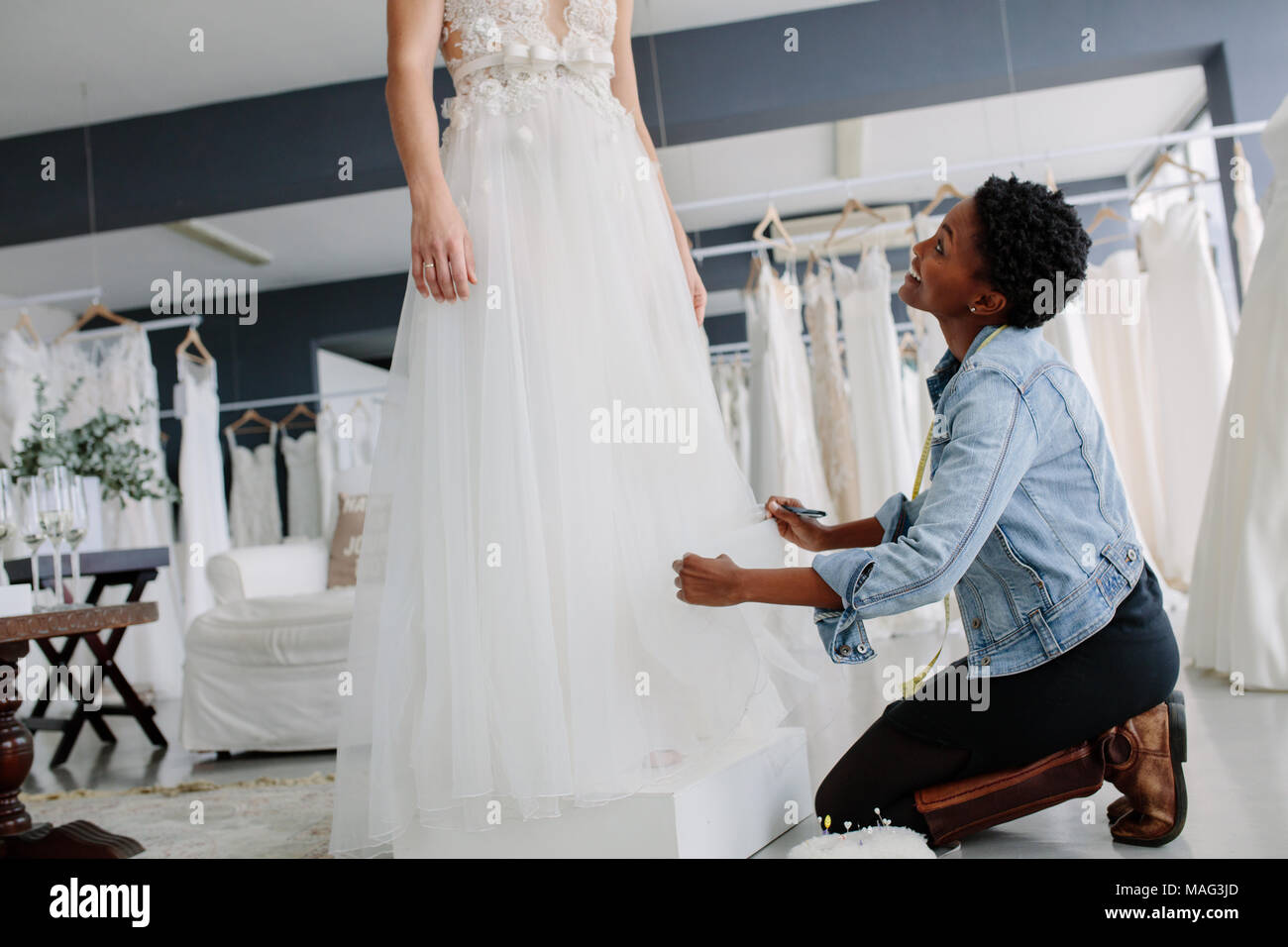 Woman making adjustment to bridal gown in wedding fashion store. Bride in her wedding dress with female dress designer making final adjustments on dre - Stock Image