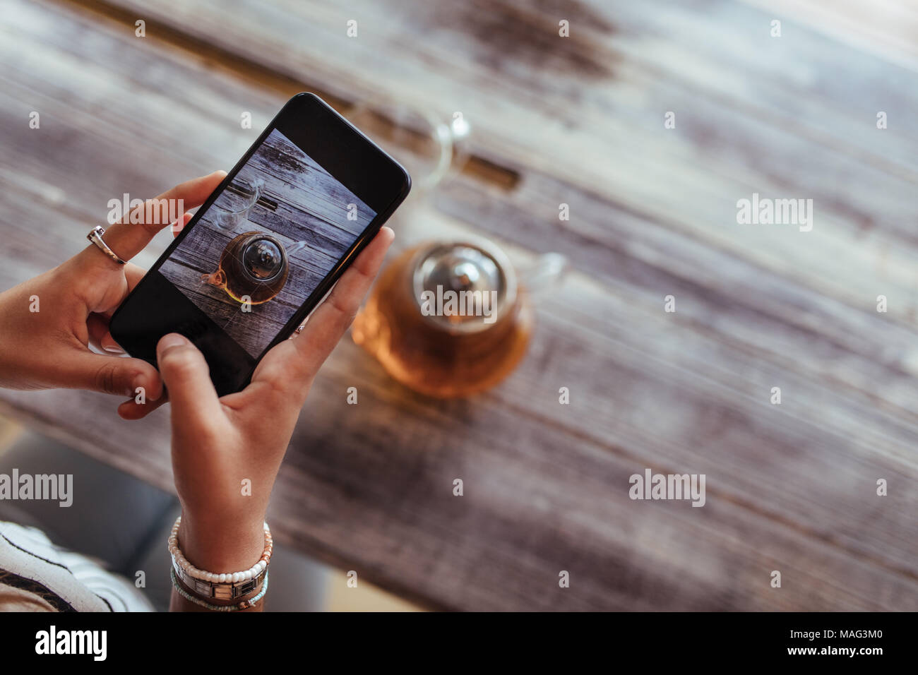 Close up of a woman capturing photos of a glass teapot using a mobile phone for her food blog. Food blogger shooting photos for her blog. - Stock Image