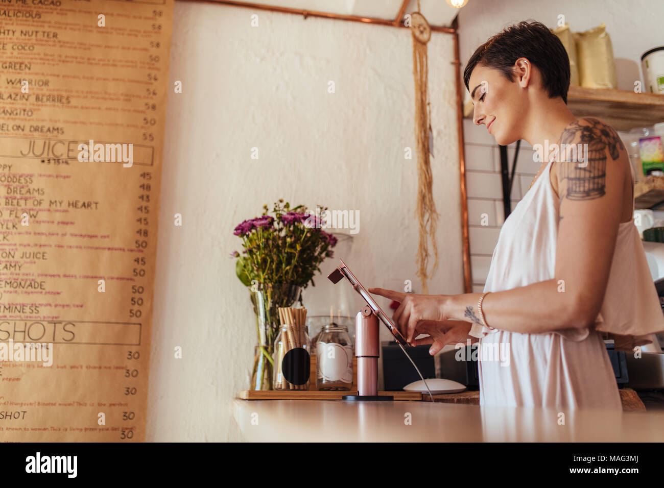 Woman standing at the billing counter of her restaurant. Restaurant owner operating the billing machine. - Stock Image
