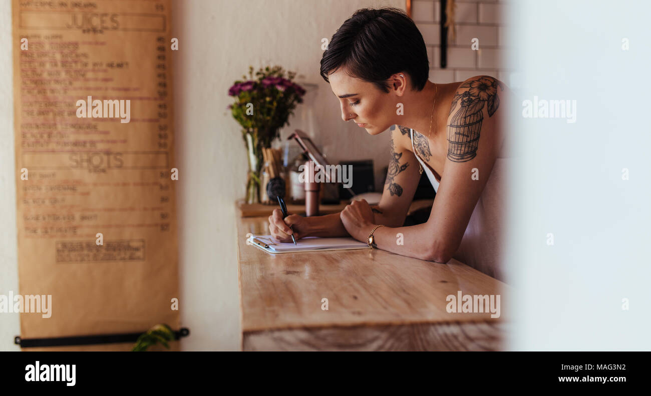 Woman standing at the counter of her cafe noting orders. Restaurant owner making notes standing at the billing counter. - Stock Image