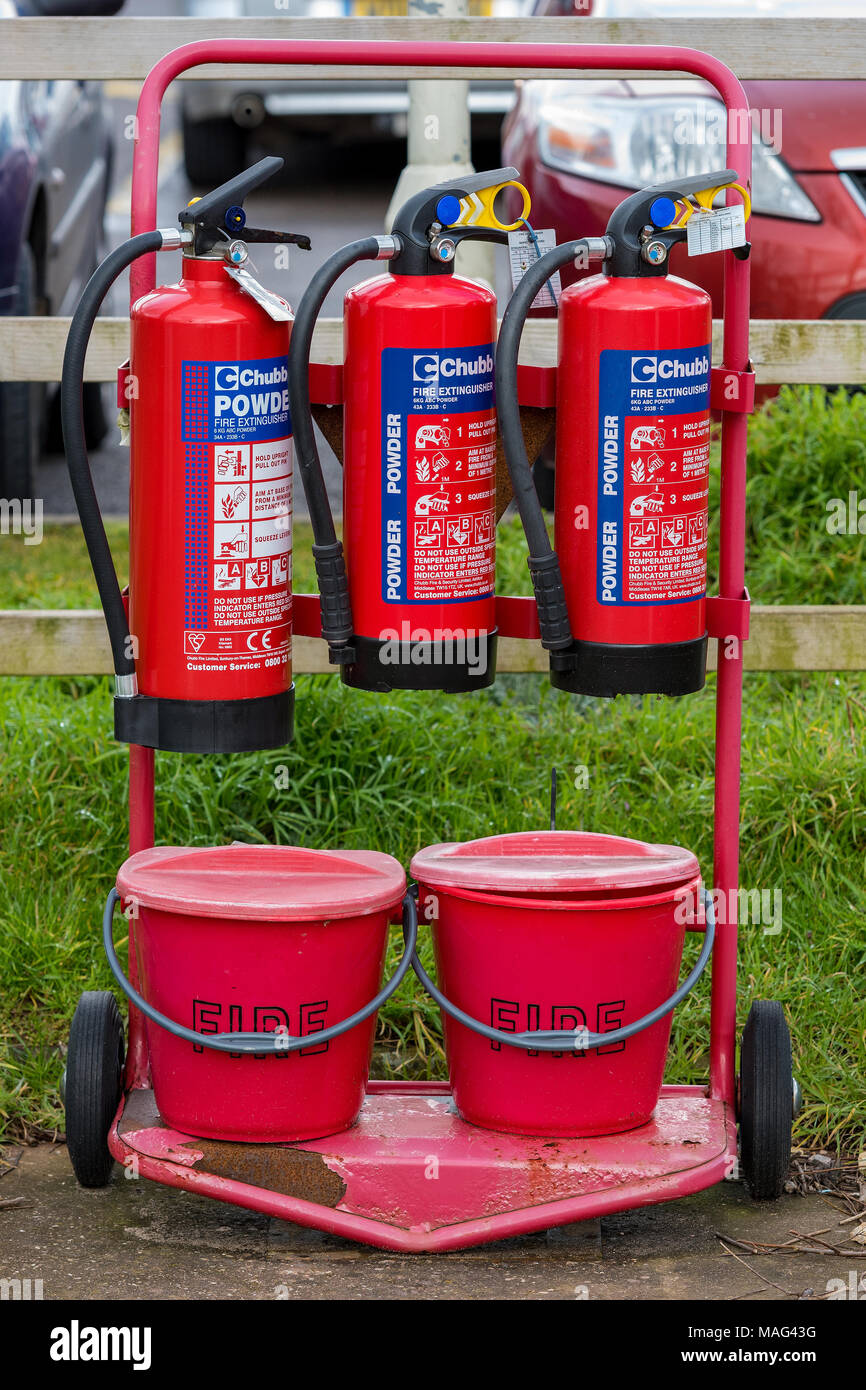 a rack containing firefighting equipment in the form of extinguishers and fire buckets full of sand at a pertrol service or filling station on roads. - Stock Image