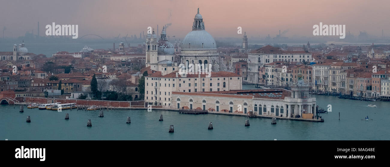 Panoramic view of Venice skyline at dusk on a clear day showing the Basilica di Santa Maria della Salute and Grand Canal. Photo taken from San Giorgio Stock Photo
