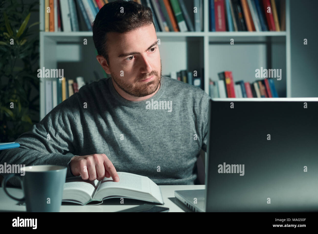 Man studying at night with book and computer - Stock Image