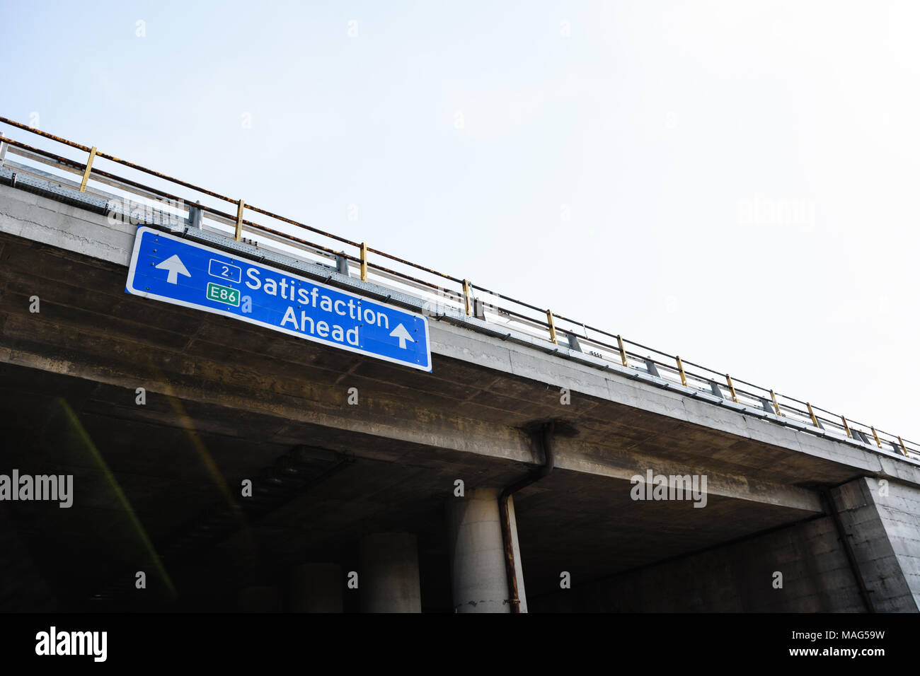 Satisfaction Ahead Blue Road Sign Against Clear Sky - Stock Image